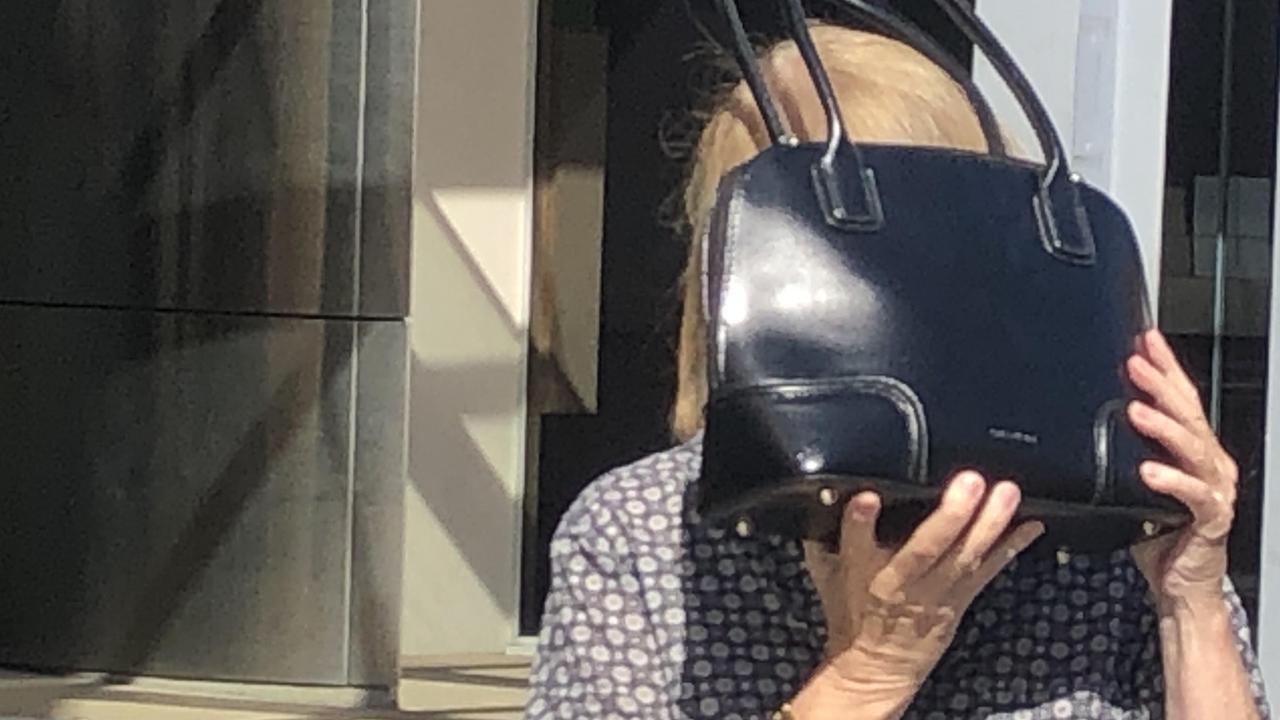 Pamela Anne Jessep hides behind her handbag as she leaves Southport Magistrates Court.