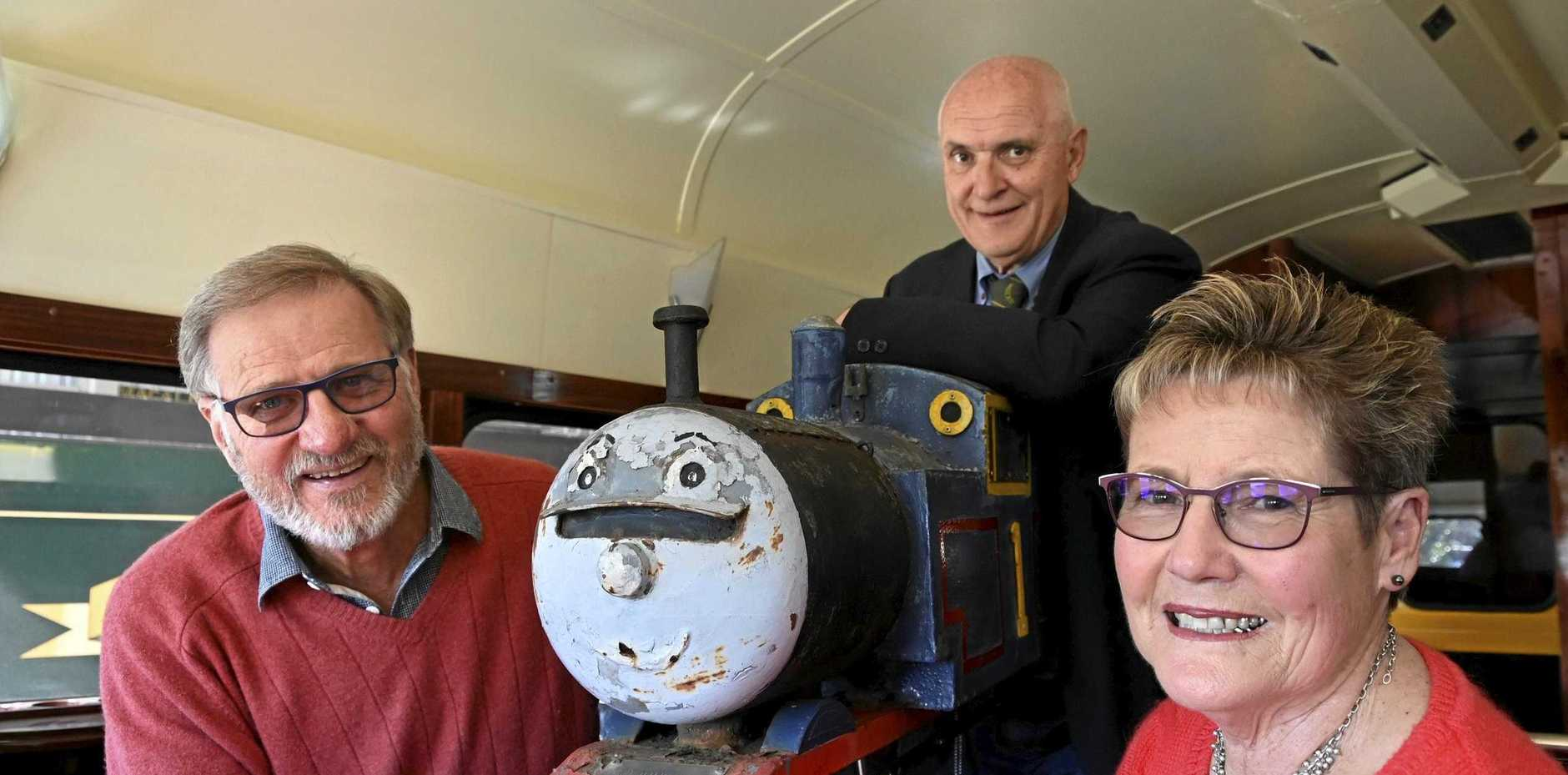 SPECIAL DELIVERY: Retired paediatrician Dr John Cox (left) delivers his unique Thomas the Tank Engine letterbox to DownsSteam's tour guide Robert Ketton and president Ros Scotney.