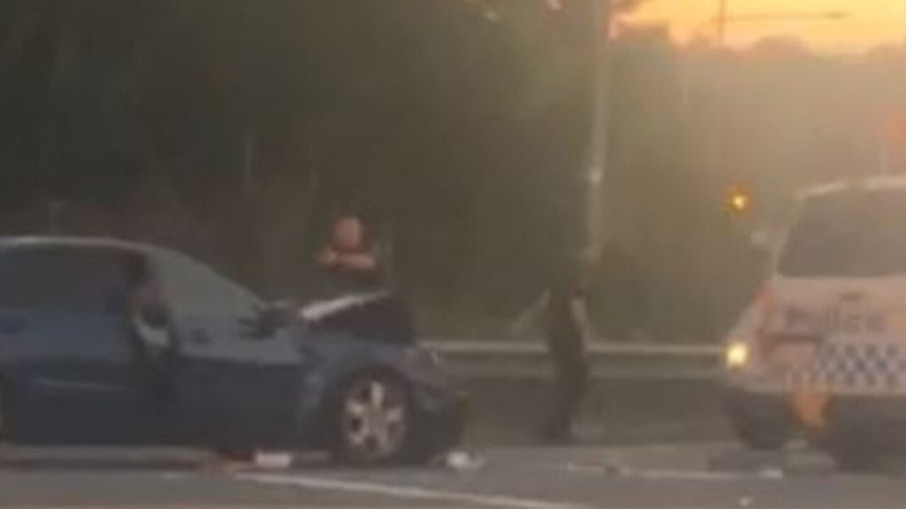 A Gold Coast police officer draws his gun on a machete-wielding motorist after he crashed his car on an M1 overpass.