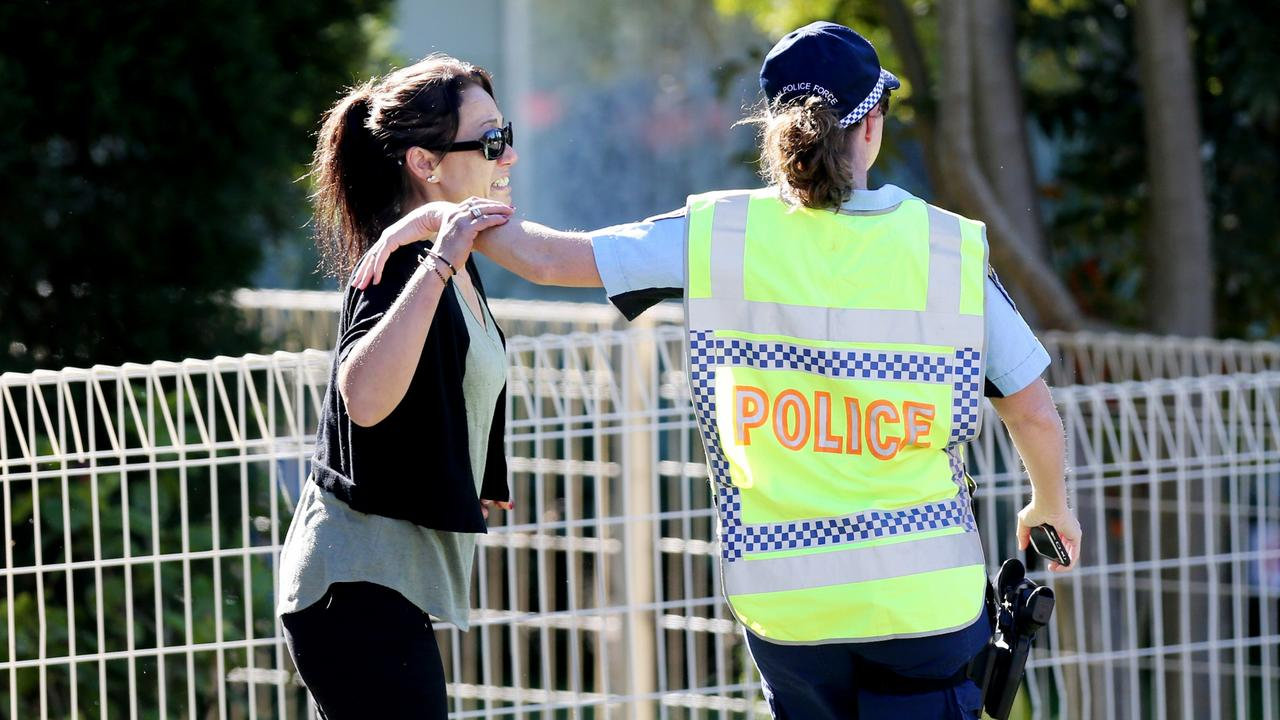 Police comfort a woman at the scene where a Year 10 male student, aged 15, died after being hit by a bus. Picture: Peter Lorimer