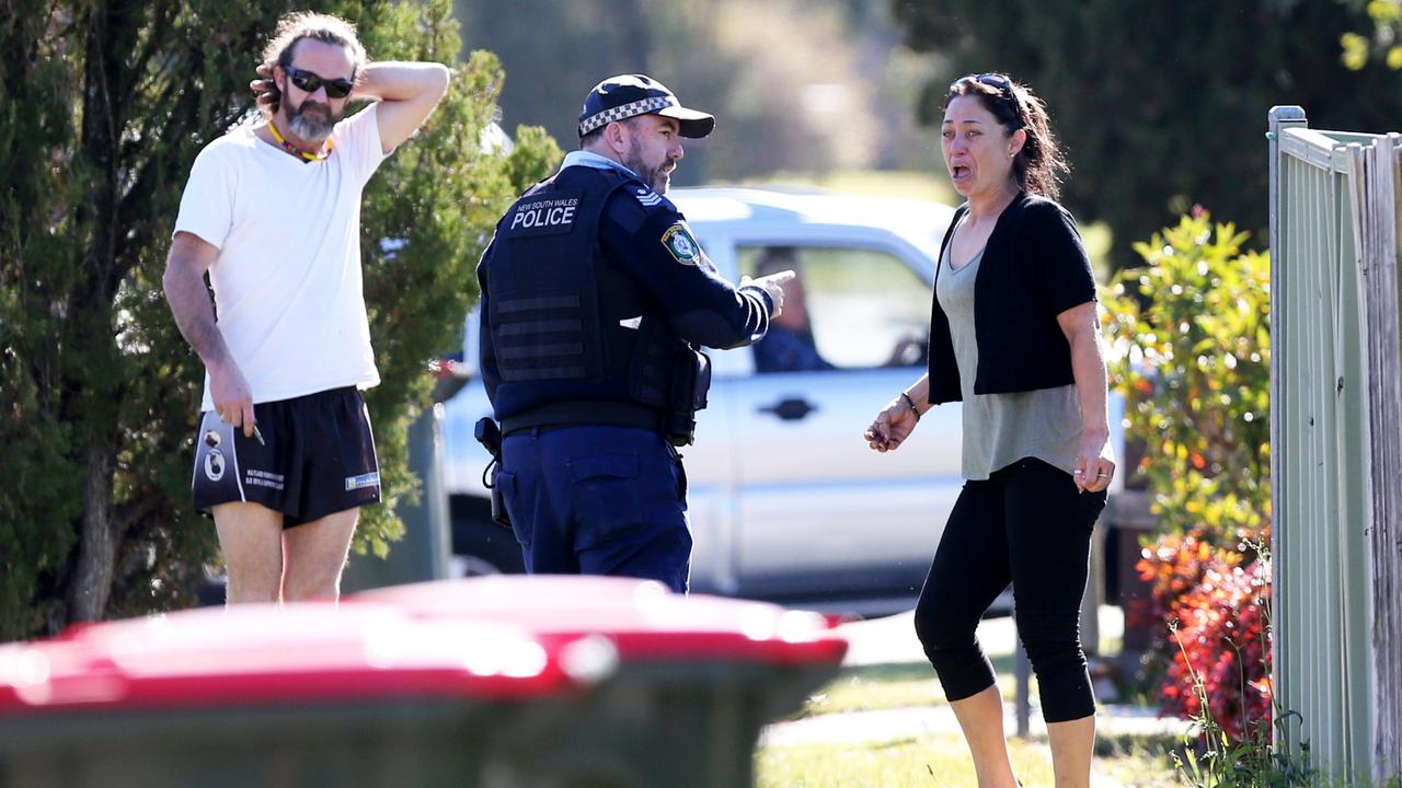 Police talk to a man and woman at the scene where a Year 10 male student, aged 15, died after being hit by a bus. Picture: Peter Lorimer