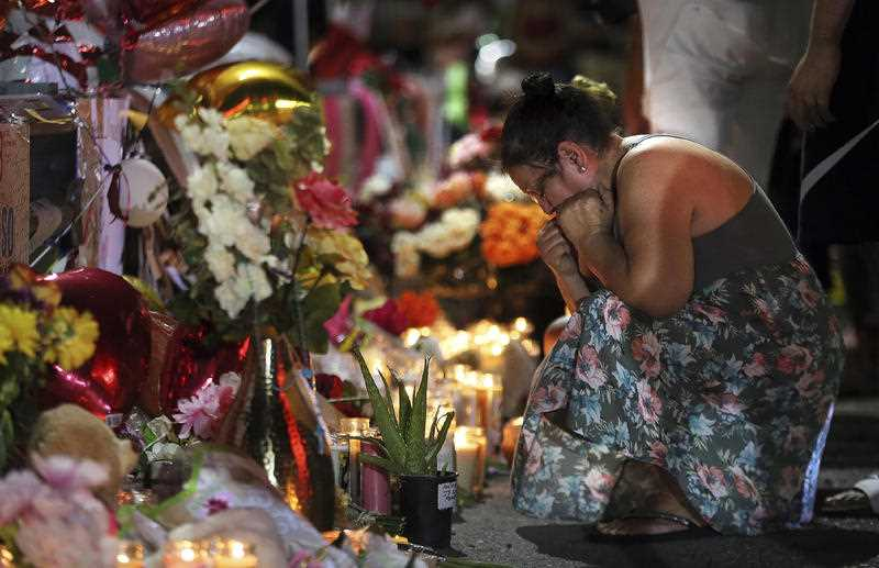 A visitor joins a vigil outside the Walmart Monday, Aug. 5, 2019, to pay their respects to those who lost their lives in Saturday's attack in El Paso, Texas.