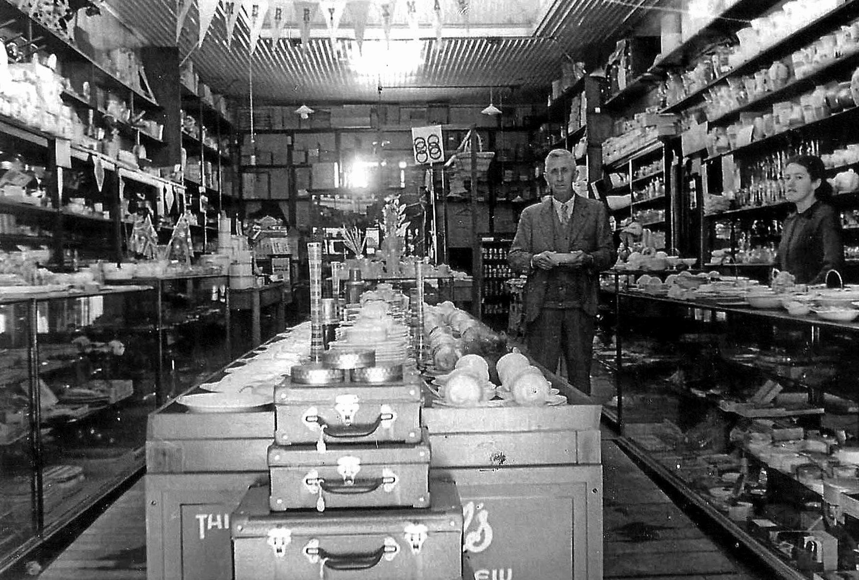 Frederick Avenell in his Avenell Bros shop, with Betty McWatters behind the counter.