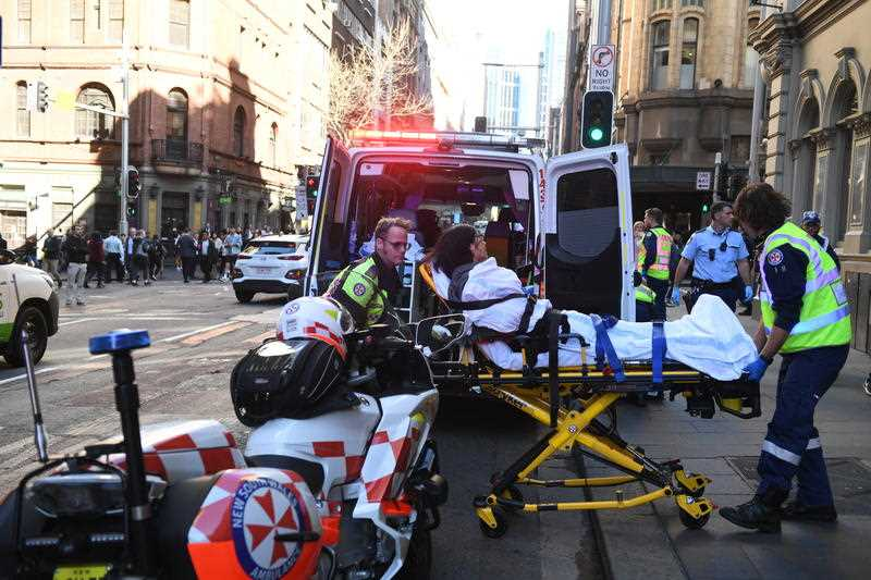 A women is taken by ambulance from Hotel CBD at the corner of King and York Street in Sydney, Tuesday, August 13, 2019. A police operation is underway in Sydney's CBD with multiple police, fire and ambulance vehicles racing to the scene amid reports of a stabbing.