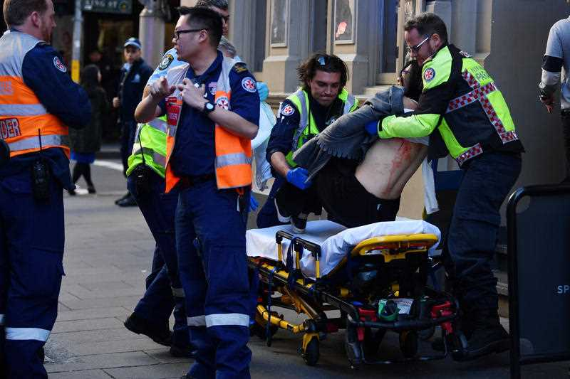 An injured woman is taken by ambulance from Hotel CBD at the corner of King and York Street in Sydney, Tuesday, August 13, 2019.