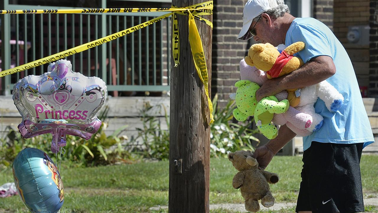Paul Laughlin places stuffed animals outside a home where five children died in a fire. Picture: AP