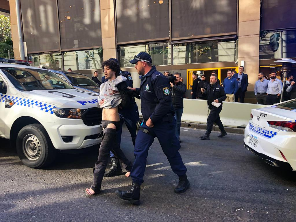 Police escort the man from the scene near Clarence Street in Sydney. Picture: Kartik Lad