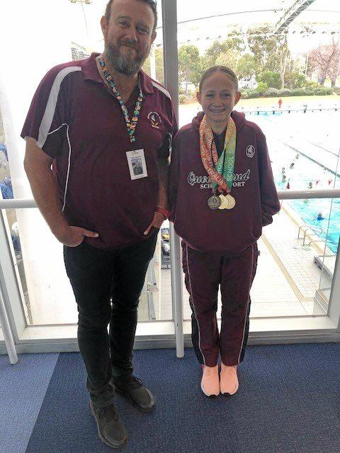 Coach Shane Kingston with young star Taryn Roberts after her three gold medal haul at the national schools championships.