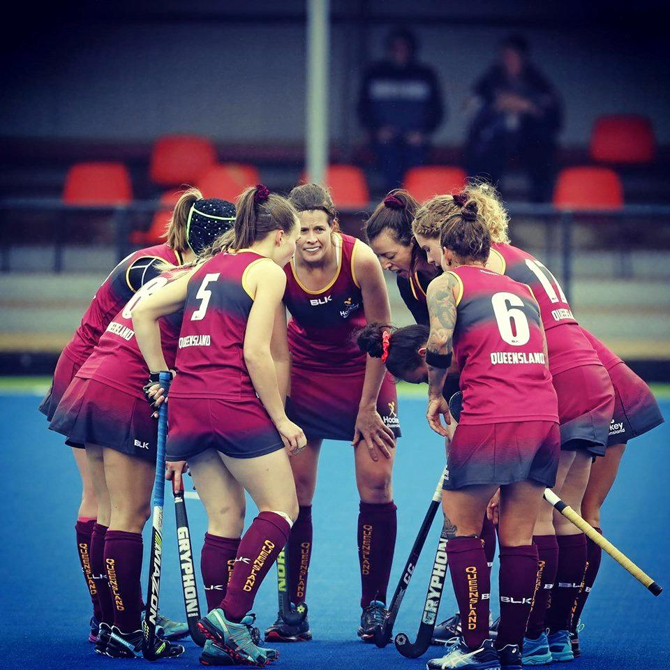 Ipswich and Queensland Country hockey player Sara Rogers (middle) forms a huddle with her gold medal-winning teammates at the Australian championships in Shepparton.
