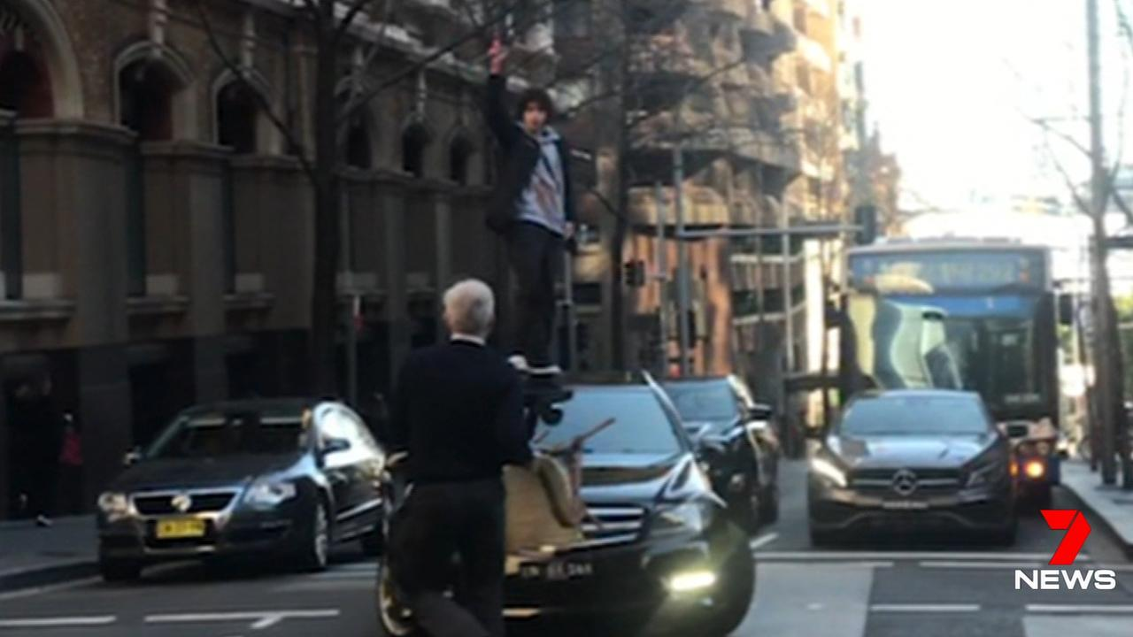 John Bamford, aka chair man, approaches Mert Ney as he stands on the bonnet of a car with a butcher's knife in Sydney's CBD. Picture: Seven News