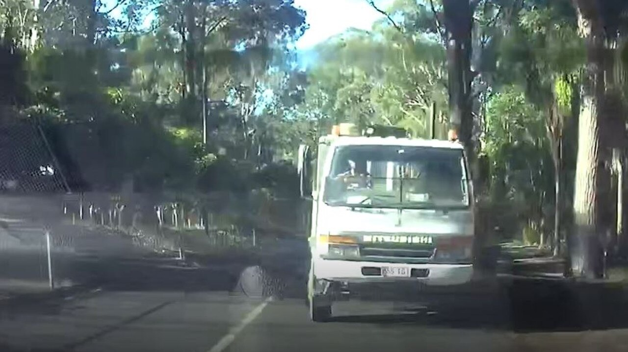 Dashcam footage shows the moment a truck driver threw an object at a woman's car on the Sunshine Coast, shattering her rear window and leaving her