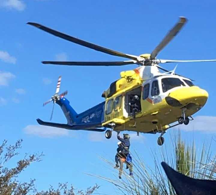 SAFE AT LAST: Teen is winched to the safety of the LifeFlight helicopter.