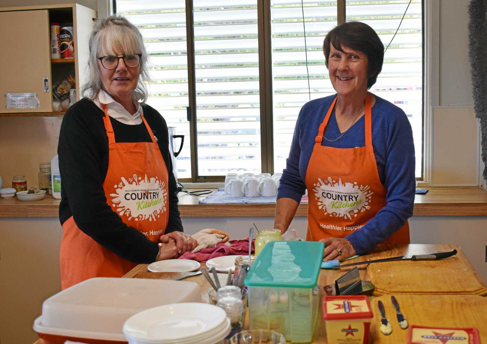 FEEDING THE MULTITUDE: Helen Van der Kleij and Lorna Cook kept the good country cooking coming as crowds ate up in the CWA building at the Imbil Showgrounds.