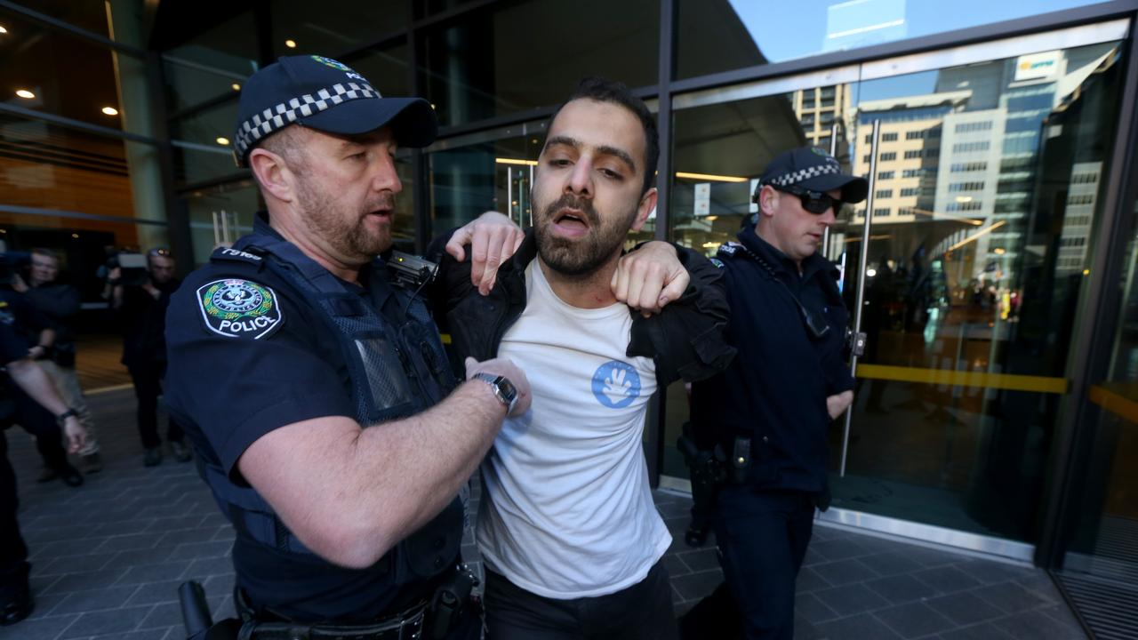 A protester is arrested by police after he tried to gain access to the South Australian Liberal party Annual General Meeting at the Adelaide Convention Centre. Picture: Kelly Barnes/AAP
