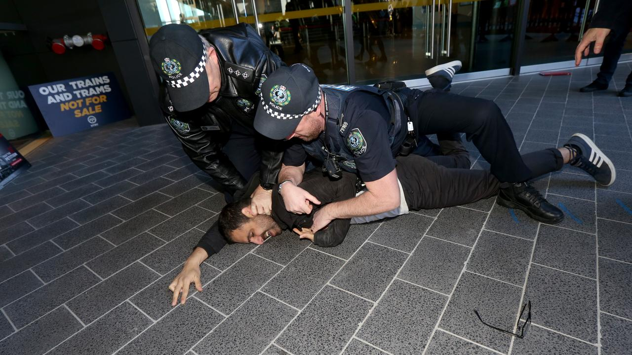 Officers arrest the protester. Picture: Kelly Barnes/AAP