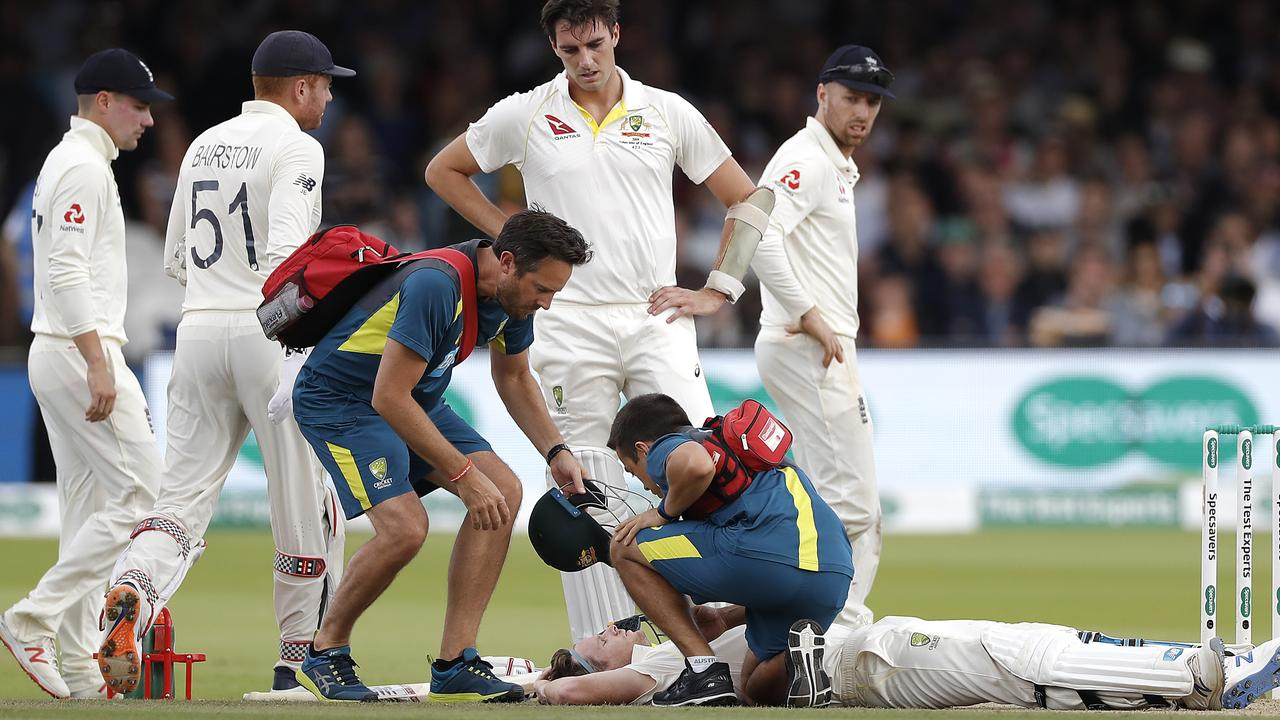 Steve Smith of Australia is assessed by Australian Team Physiotherapist David Beakley and Australian Team Doctor Richard Saw after he was struck by a delivery from Jofra Archer of England.