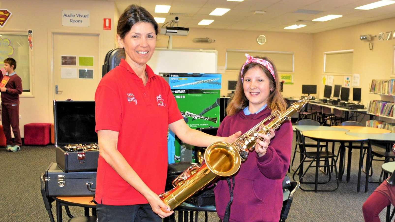 HELP IN HARMONY: Robyn Thomson presents Warwick Central State School's Stella Leslie with her brand new tenor sax.