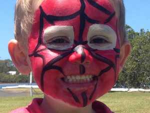 Child wearing Spider-Man suit seen in car