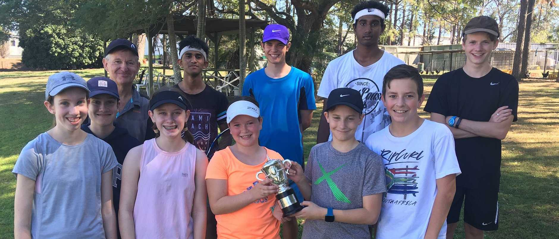 Ashleigh Barty's French Open trophy replica with some of the juniors at her spiritual home of the West Brisbane Tennis Centre. Also in the picture is Jim Joyce, back left, Barty's mentor and junior coach.