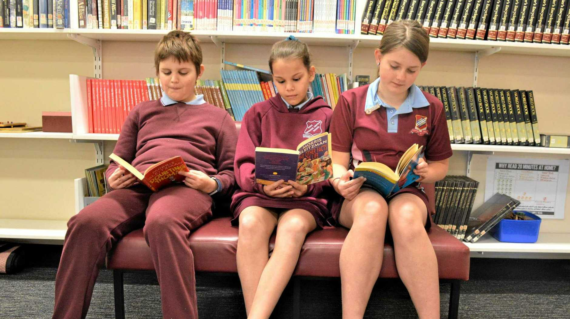 BOOKWORMS: Linkin Parsons, Emillie Rowley and Lacey Balloch enjoy the new donation of books.