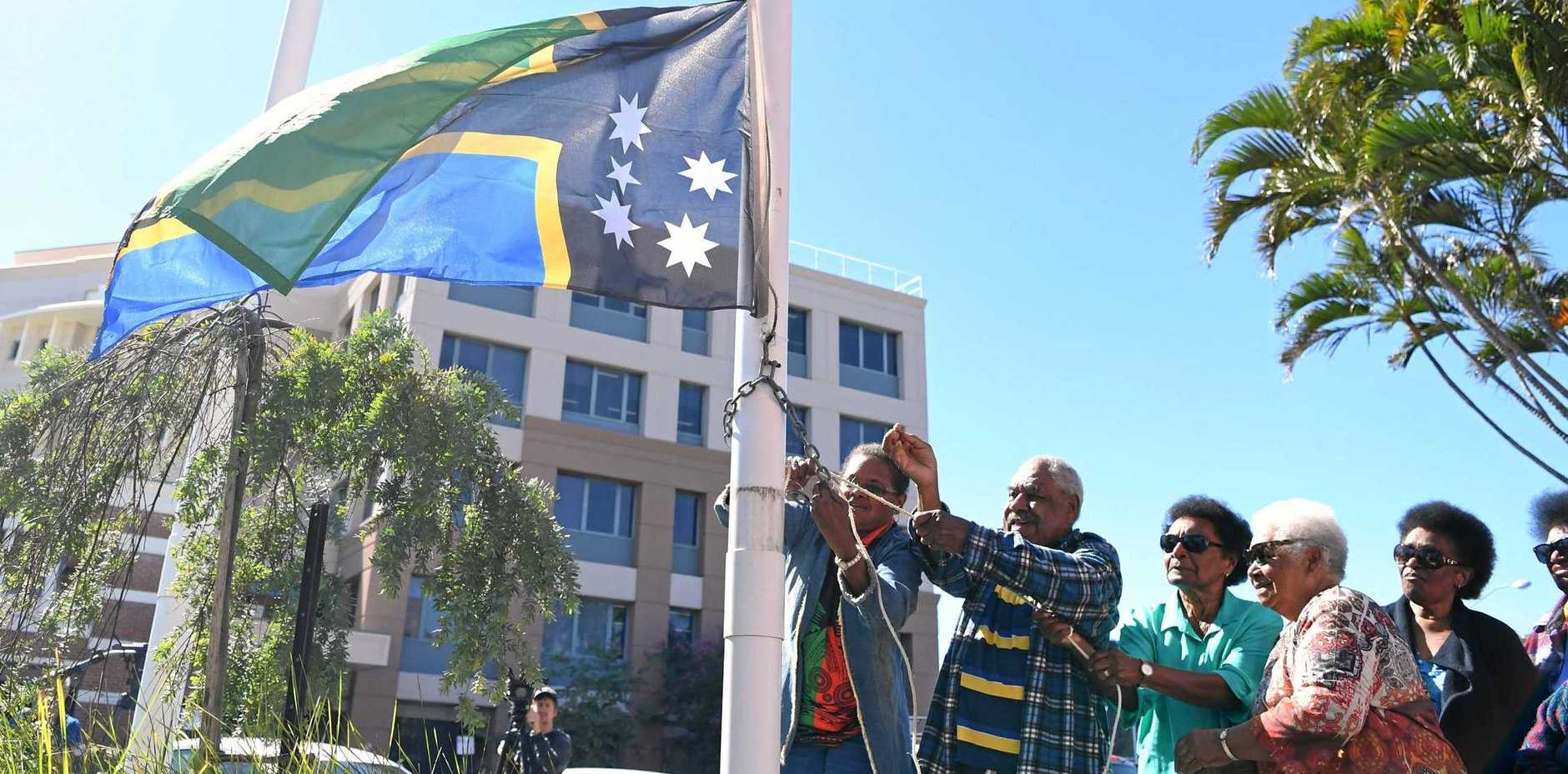 PROUD: Elders raise the flag at celebrations to mark 25 years since the Federal Government officially recognised ASSI as a distinct cultural group