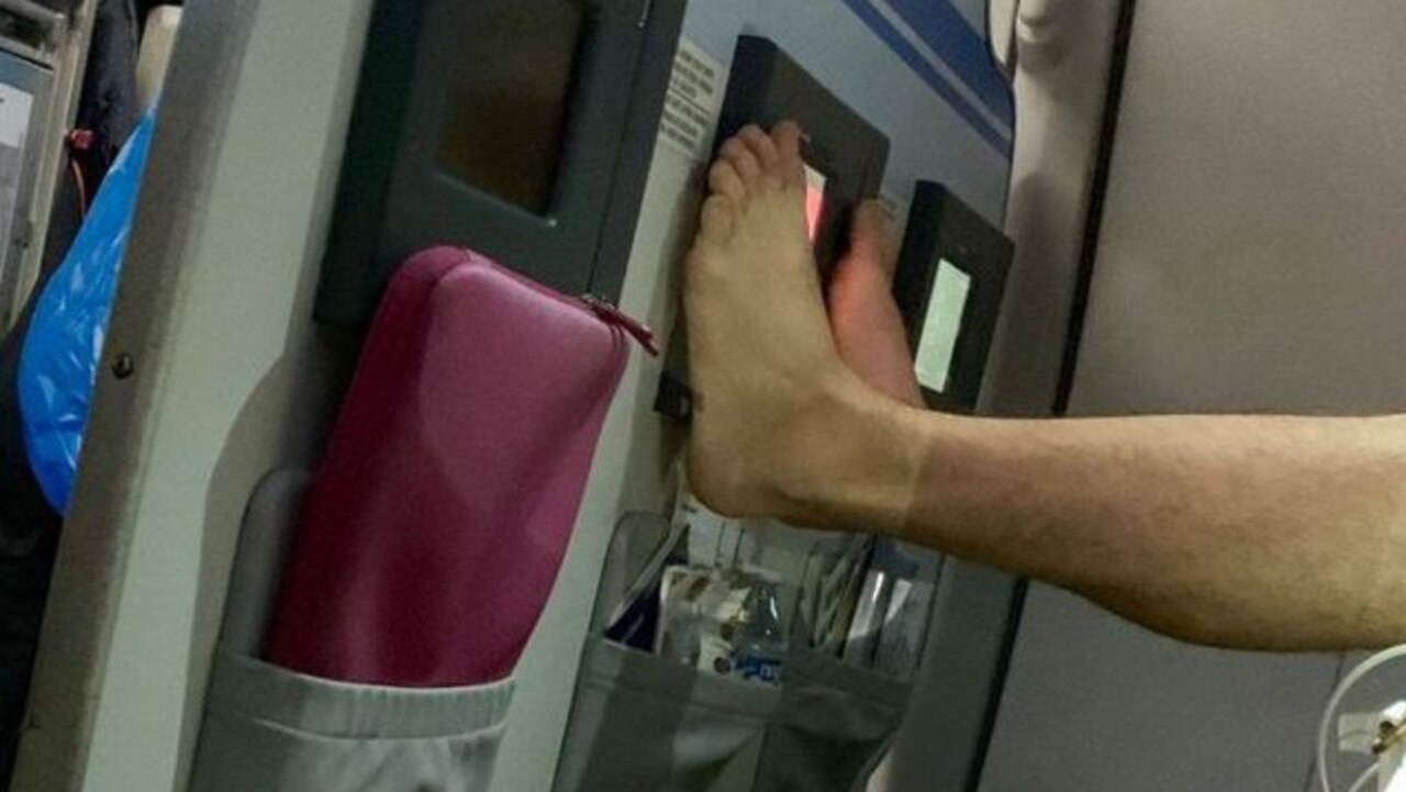 A passenger was caught putting his dirty toes on the plane entertainment screen. Picture: Andy Richter