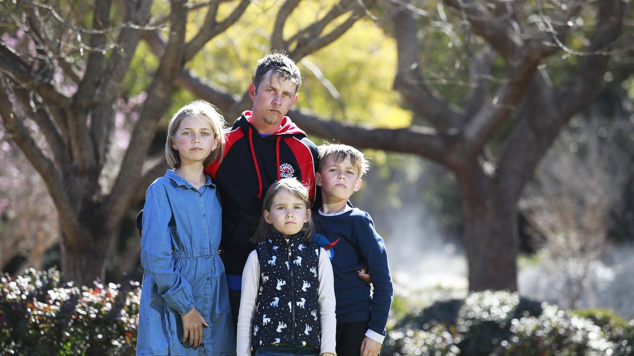 Daniel Foulds with his children Lily, 11, Cory, 10 and Indy, 7, at The Japanese Gardens in Toowoomba. They all had their flu shots on Wednesday (AAP Image/Claudia Baxter)