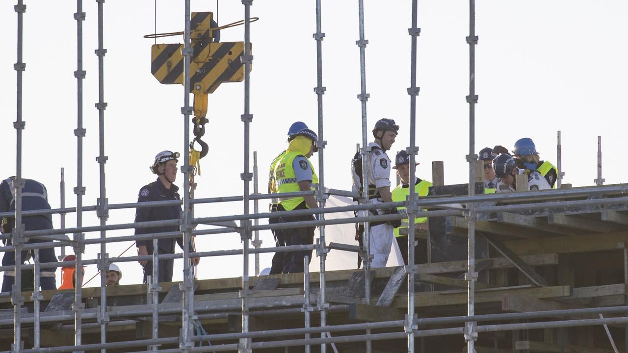 Police and emergency service workers in hard hats on the roof of the building. Picture: Dylan Robinson