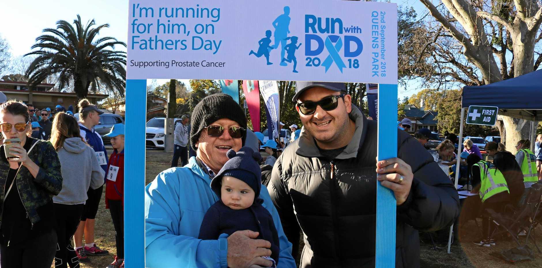 FUN RUN: Three generations of Toowoomba blokes (from left) grandfather Tim Ryan holding his grandson Huxley Ryan, next to his son Dominic Ryan, at the 2018 Run with Dad fun run.