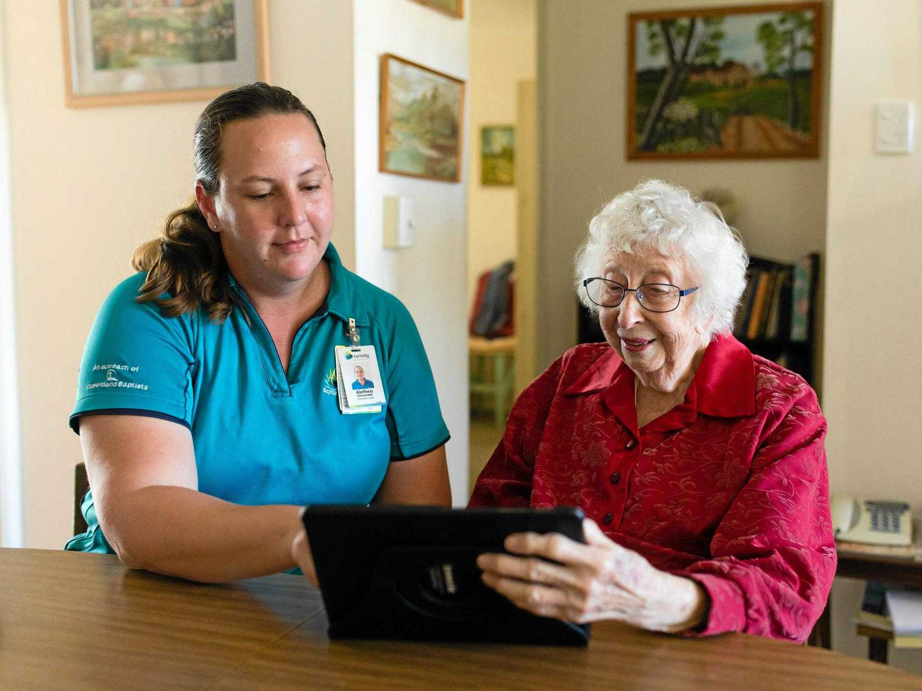 TECHNOLOGY: Carinity Home Care Rockhampton Lifestyle Carer Alethea Giovannini assists Beverley Young with her Mobi tablet.
