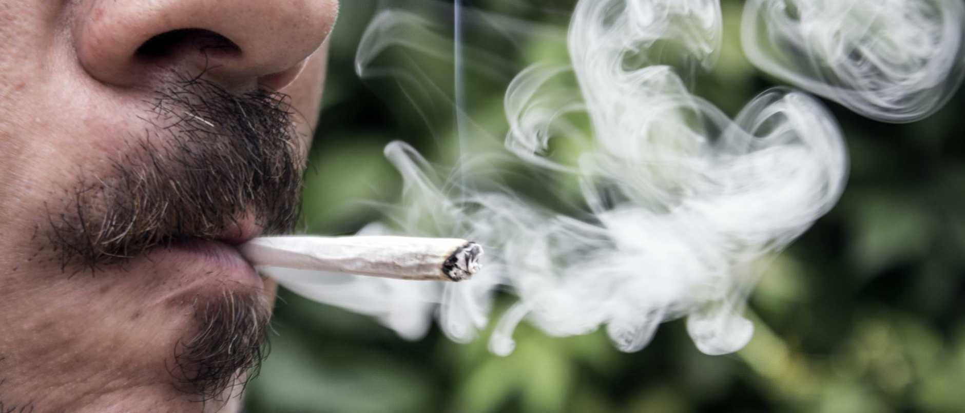 man smoking a marijuana joint