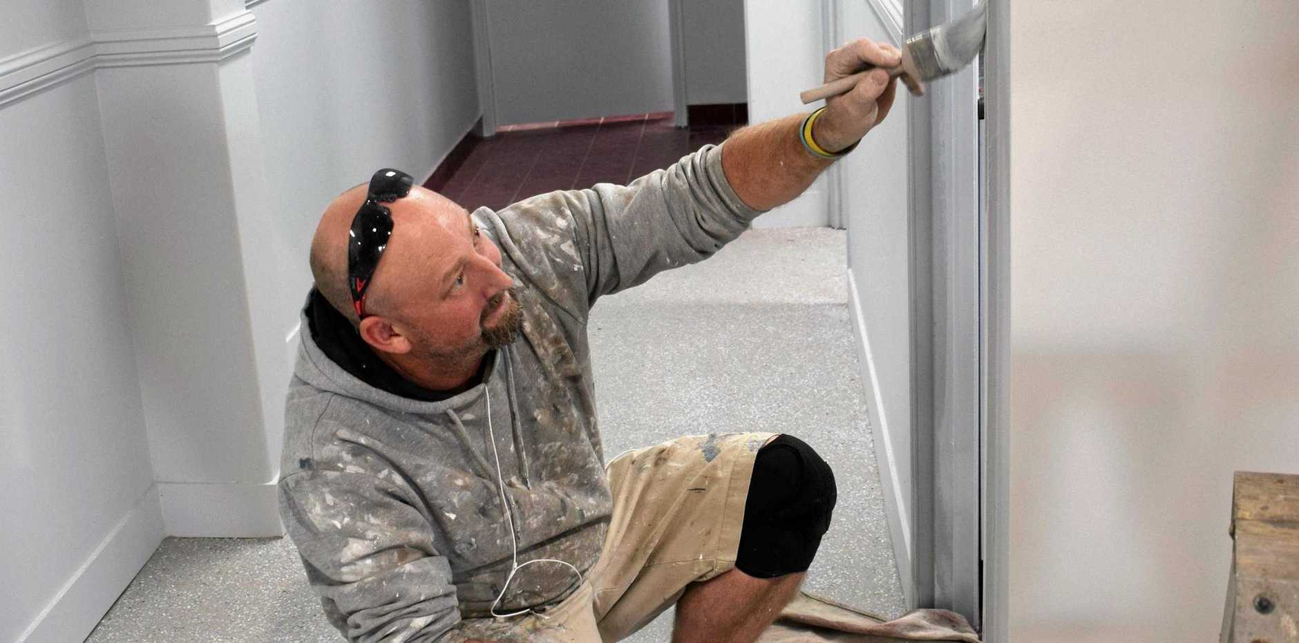 Painter Paul Olsen from Tony Hehir Painting puts the finishing touches on some of the office space in the new building.