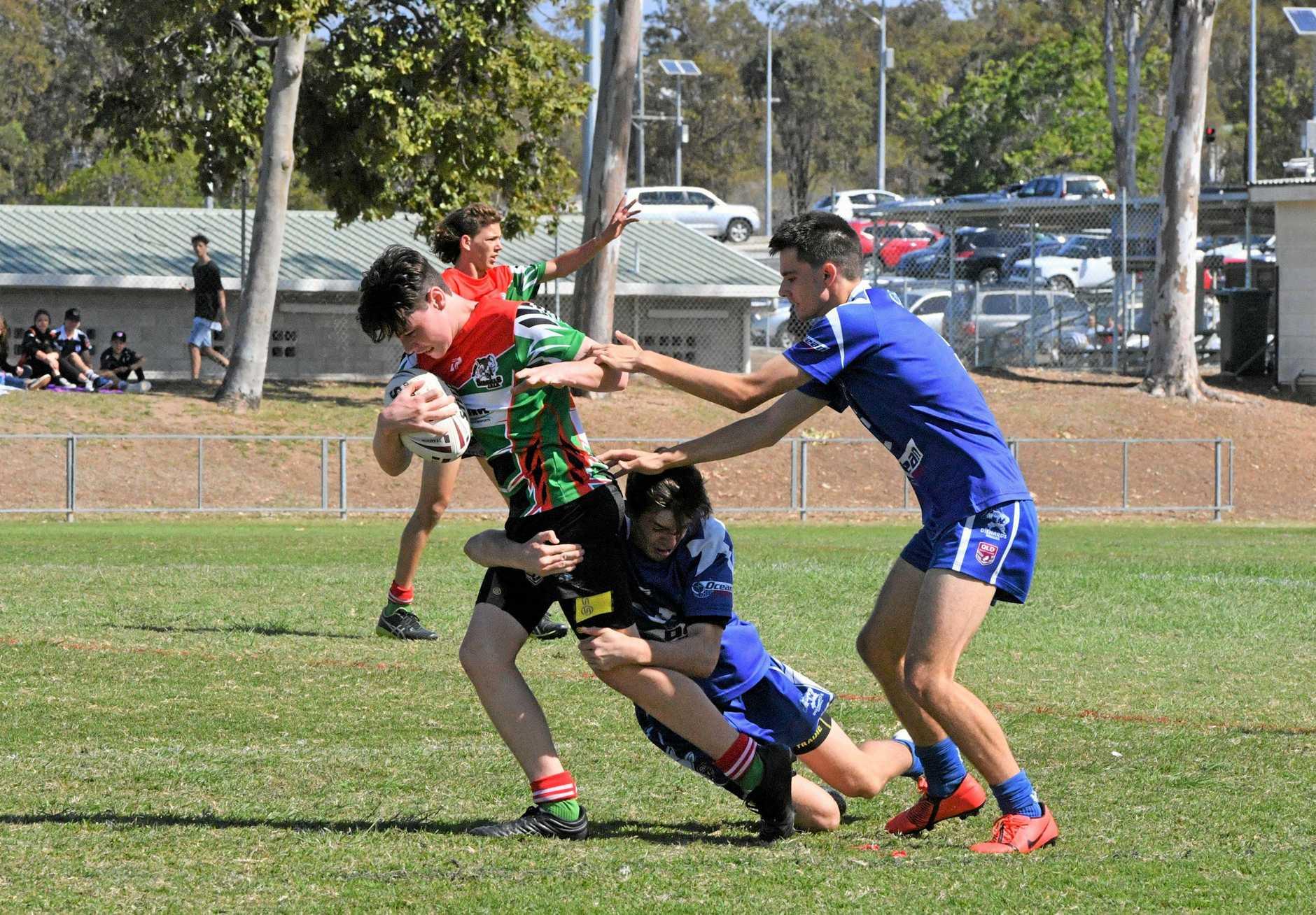Tannum's U15 player Jack Westlake, Valleys players Logan Slade (around legs) and Ethan Malone.