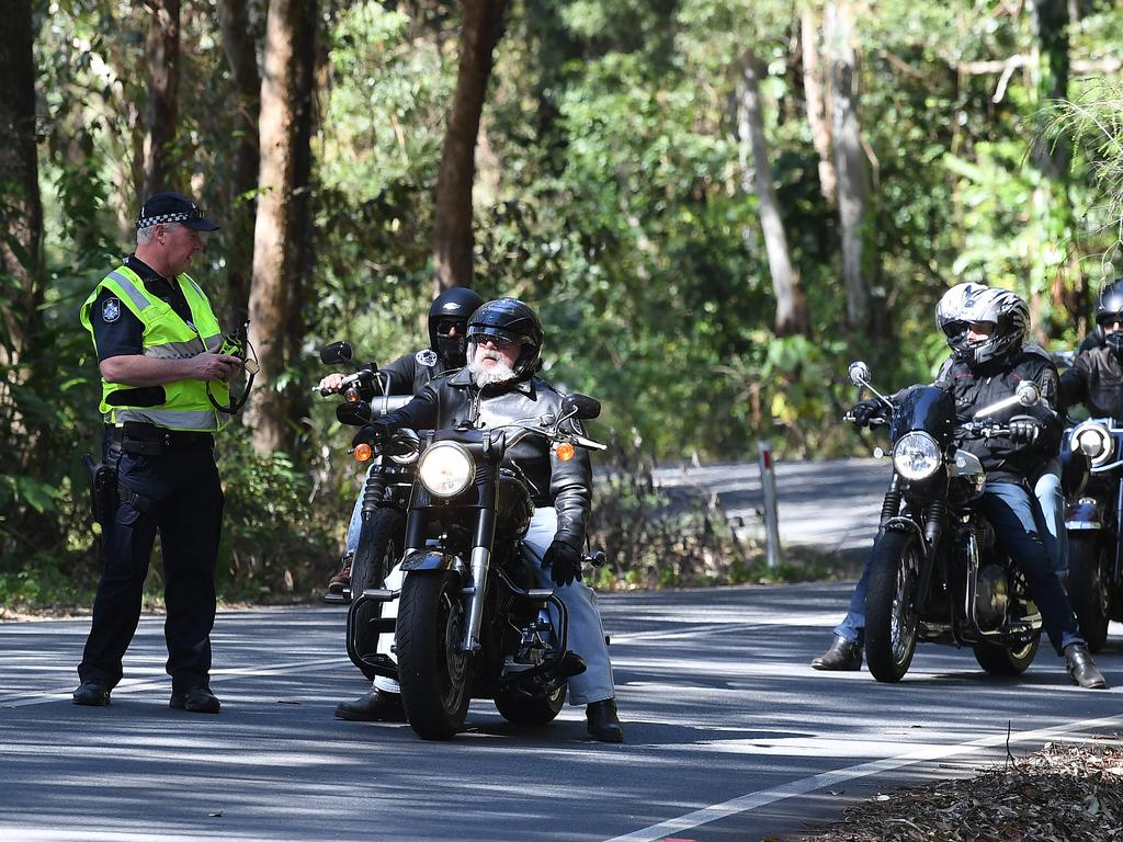 Motorcycle riders wait for the road to be cleared at the scene of a fatal motorcycle accident on Maleny Stanley River Rd, Booroobin.