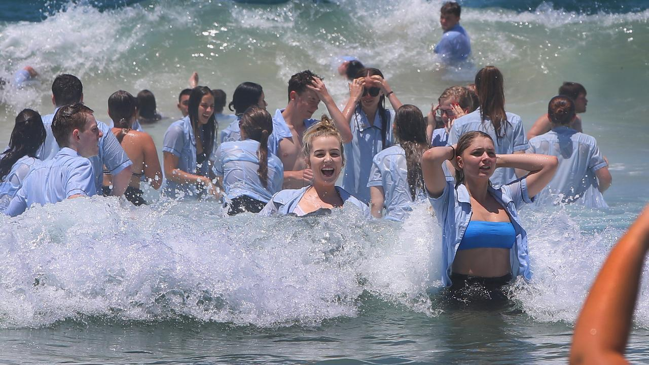 Nerang State High seniors swimming their uniforms at Surfers Paradise on the last day of school. Picture: Glenn Hampson.