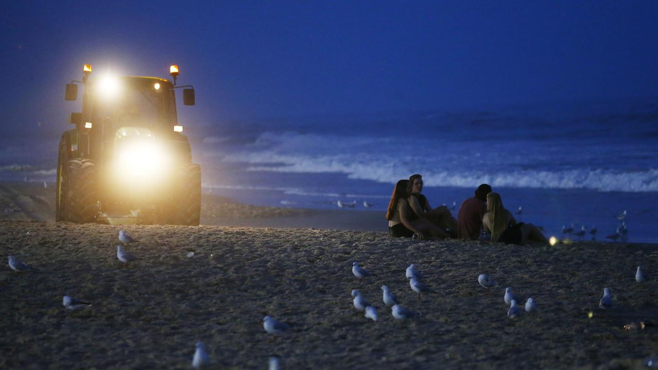 A council clean-up tractor near schoolies at Surfers Paradise Beach. Photo: Jason O'Brien.