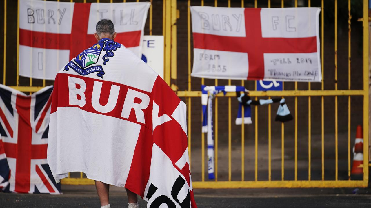 A fan holds a vigil at Bury's Gigg Lane ground.