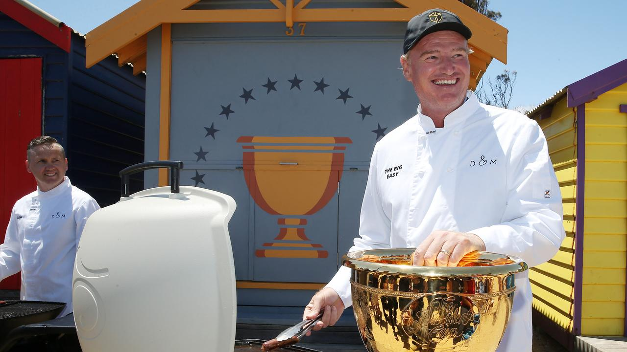 International team captain Ernie Els cooks up some sausages at Brighton Beach ahead of the Presidents Cup. Picture: Michael Klein