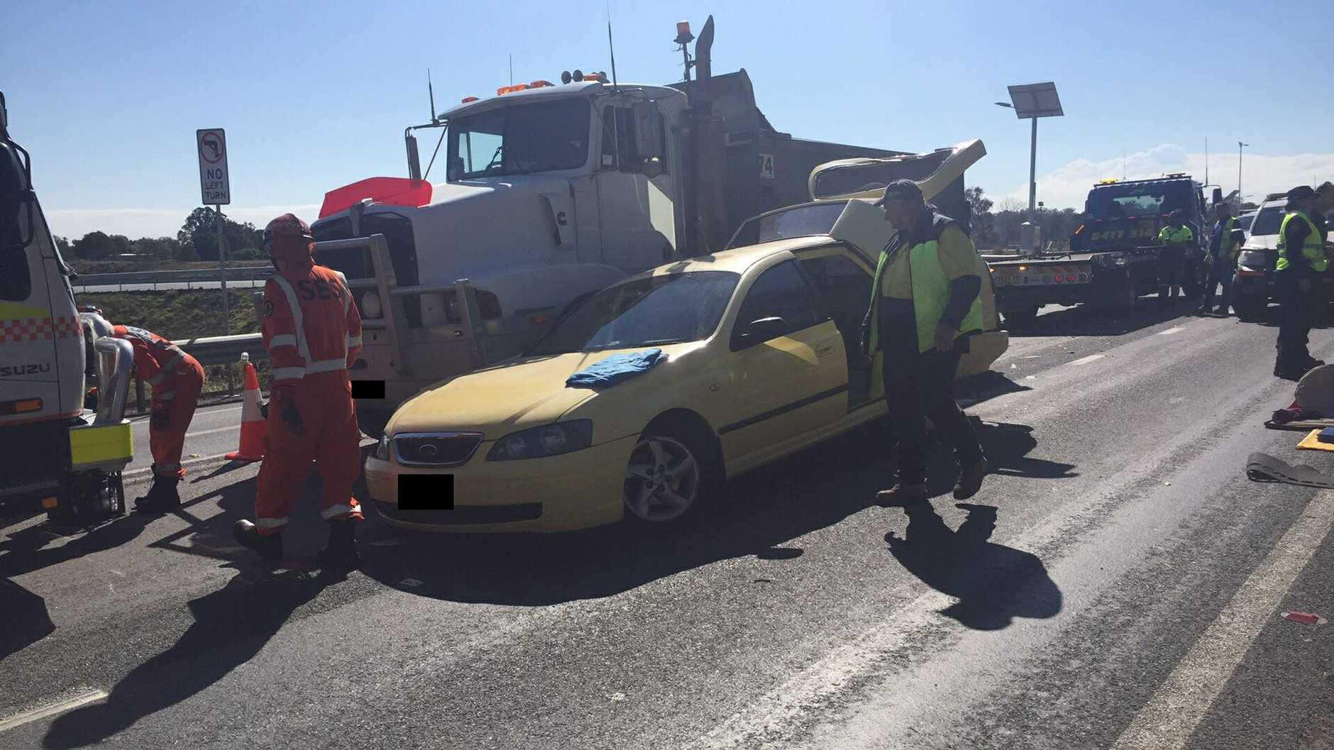 Emergency services respond to a collision between a truck and a car on the Pacific Highway near South Grafton.
