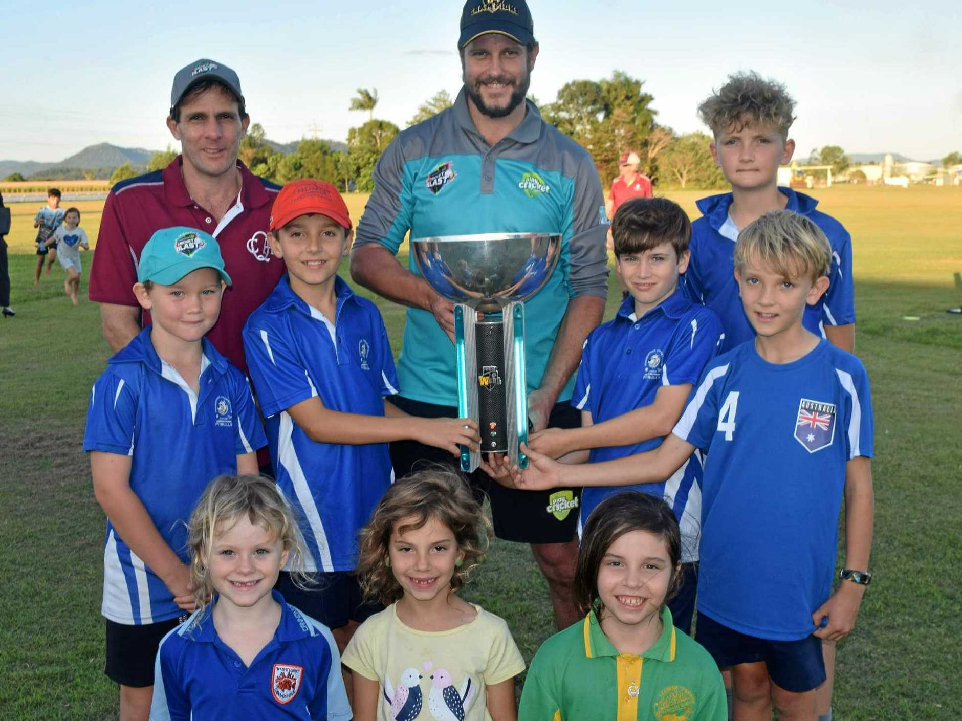 Retired Queensland and international test cricketer Brendan Nash, Queensland Cricket area manager Blake Rutherford with the WBBL trophy and Proserpine Junior Cricket players Archer Philipson, (middle) Emerson Baker, Oliver Wilson, Angus Hardy-Young, Nicholas Philipson, (front) Chiara Johnson, Zahra Kale and Hartley Kale.
