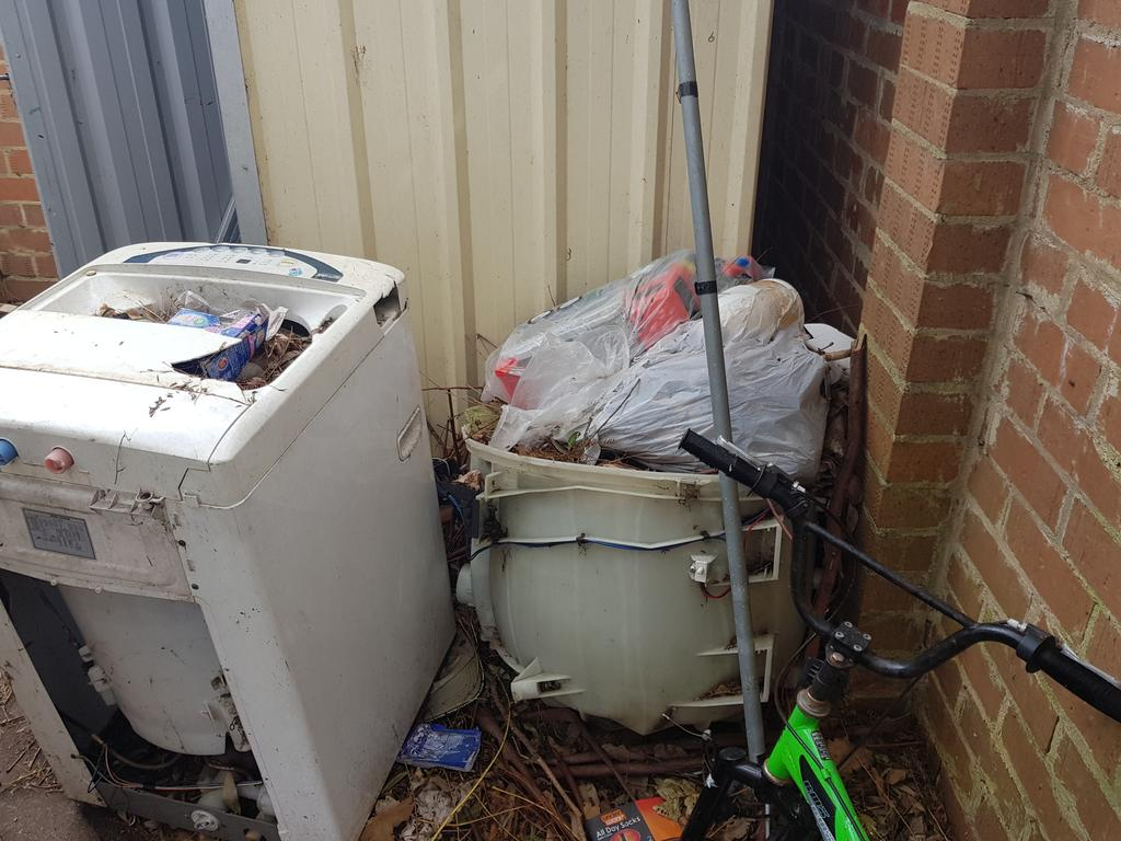 Bags of rubbish and a broken old washing machine in the back yard.