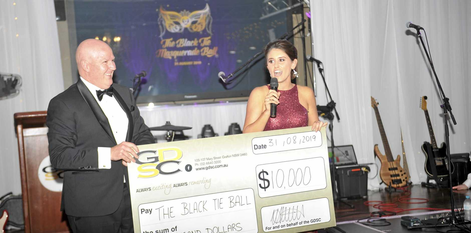 GAINING MOMENTUM: Nathan Whiteside from Grafton District Services Club presents Black Tie Ball founder Emma Joseph with a cheque for $10,000. This year's fundraising recipient is Grafton's Men's Shed.