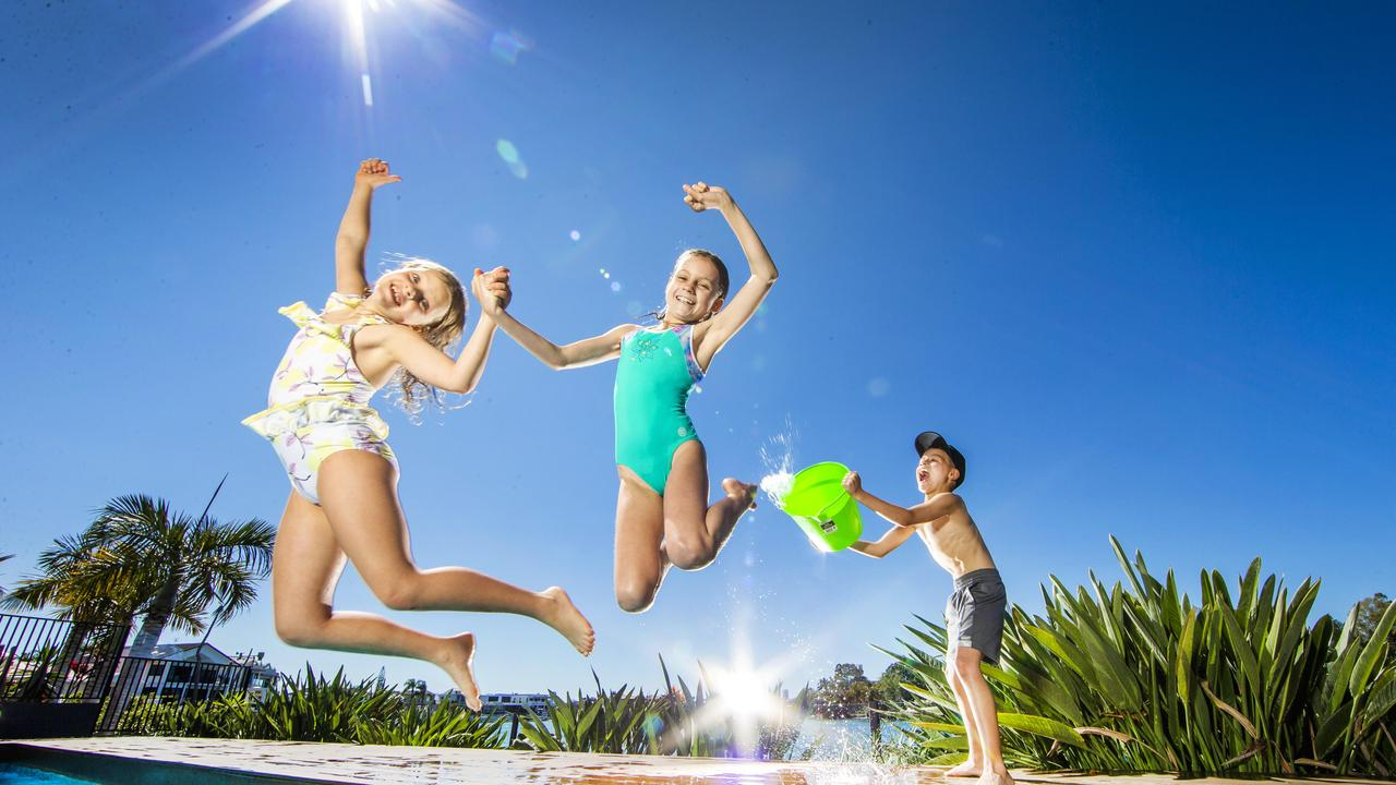 Scarlett Shannon, 9, from Southport and Ashley Chambers, 9, from Sorrento,cool off in the swimming pool while Darcy Chambers, 7 throws water. Picture: Nigel Hallett