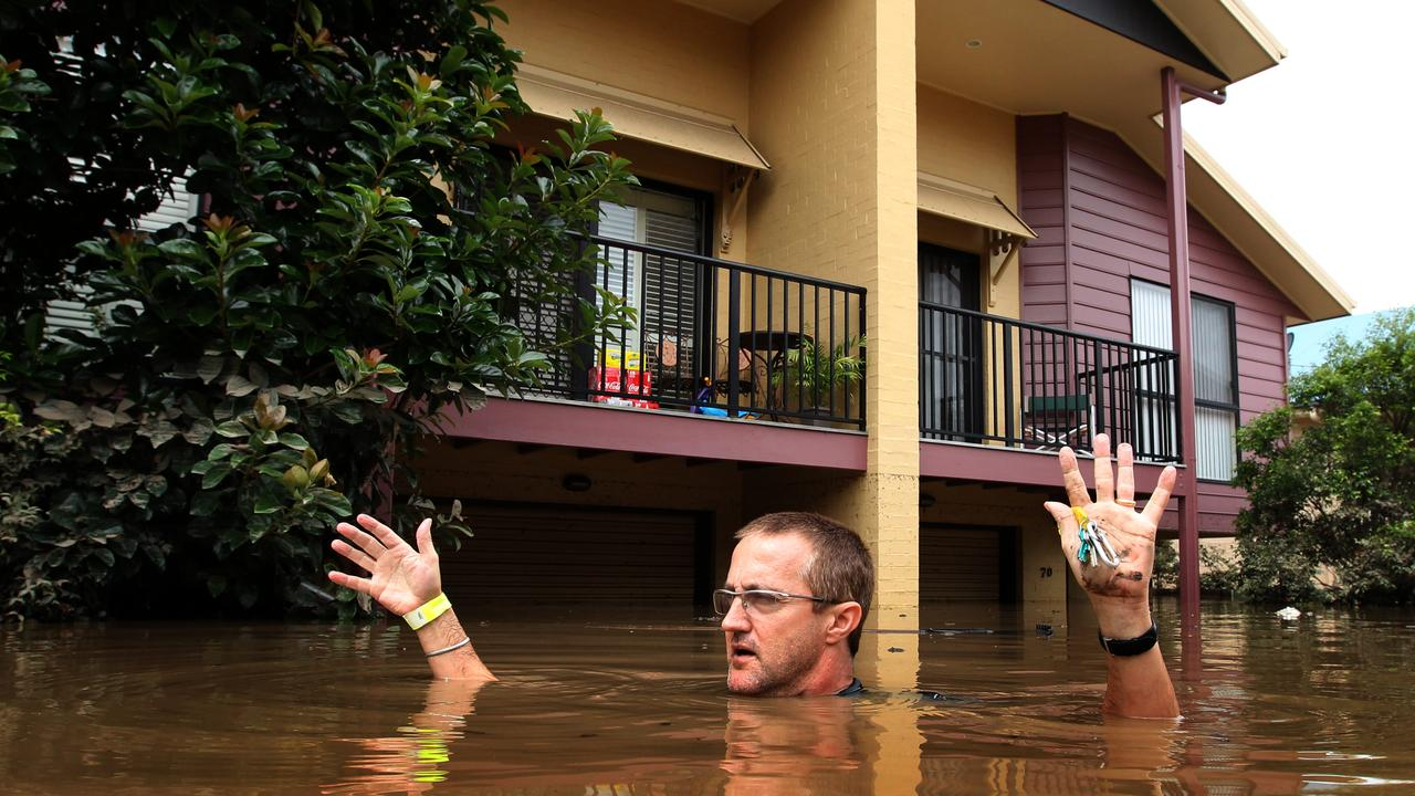 Glen Middleton returns to his house in his flooded street in Graceville during the 2011 floods.