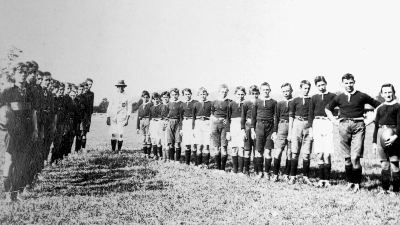 Nambour Rural School's footballers facing their opposing team, Nambour, ca 1920. Pictured in the line-up of the Nambour Rural School's team (right) include Jim Grimes, fifth from front.