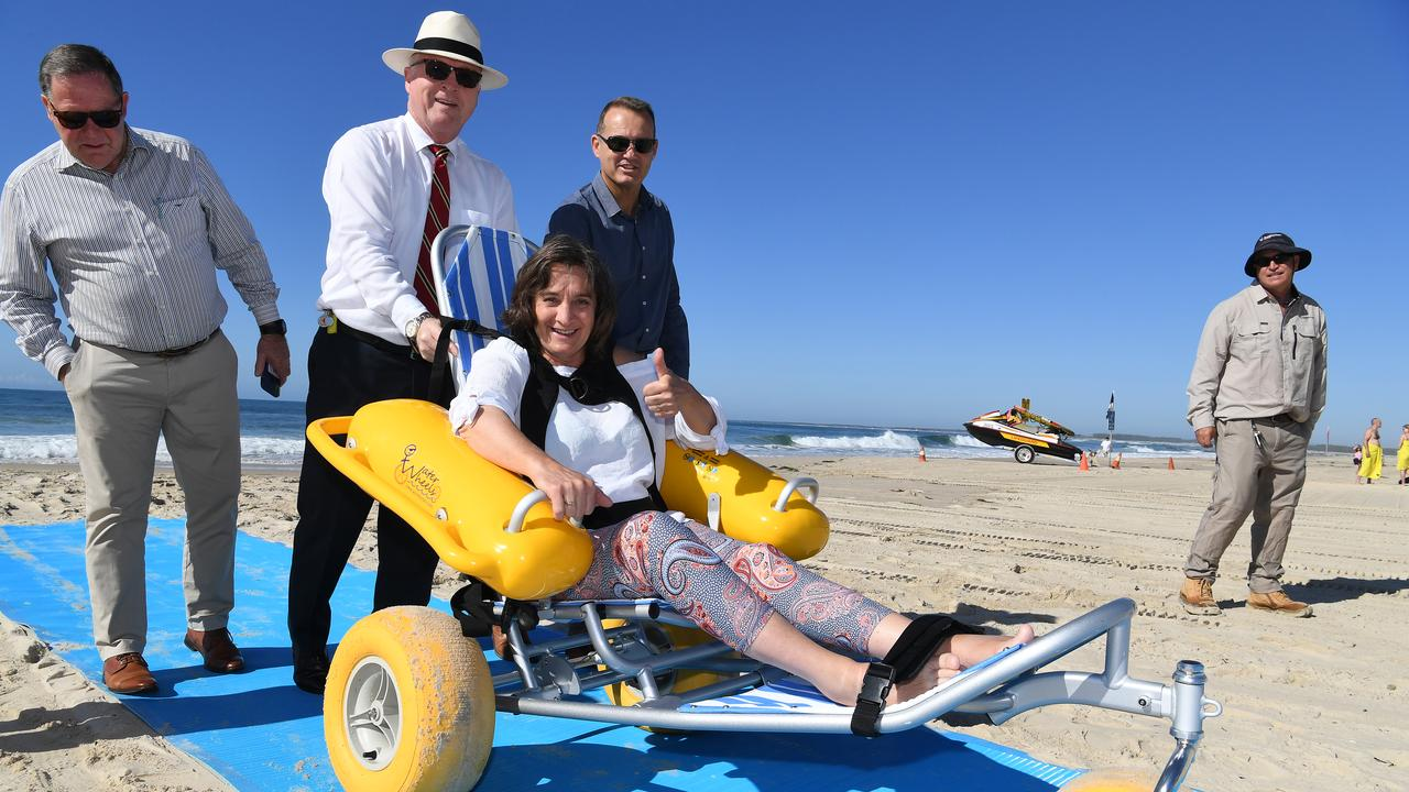 Jo Ellsum tests out the new beach mat with the help of Councillor Greg Rogerson, Mayor Mark Jamieson and Councillor Peter Cox.