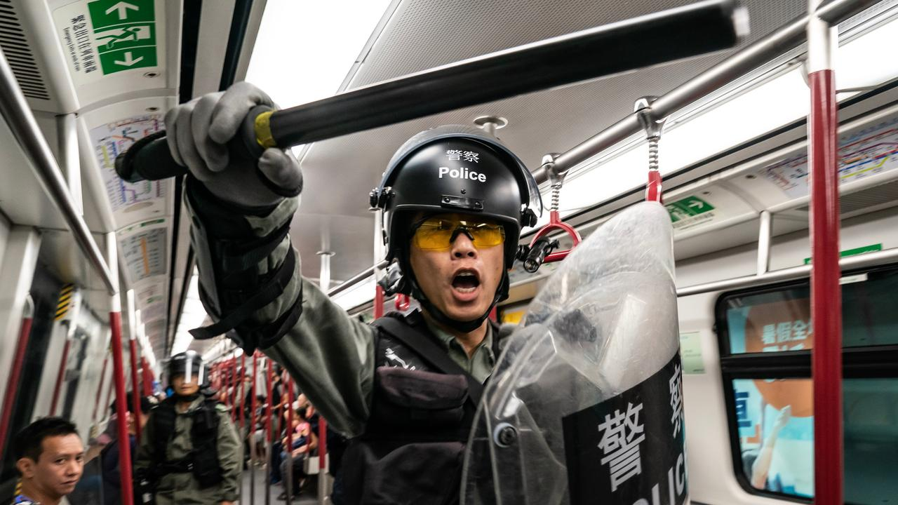 Riot police charge in a train at the Tung Chung MTR station after protesters blocked the transport routes to the Hong Kong International Airport.