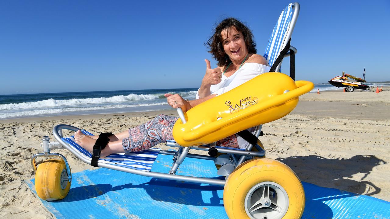 THUMBS UP: Jo Ellsum tests out the new beach mat at Metropolitan Caloundra SLSC.