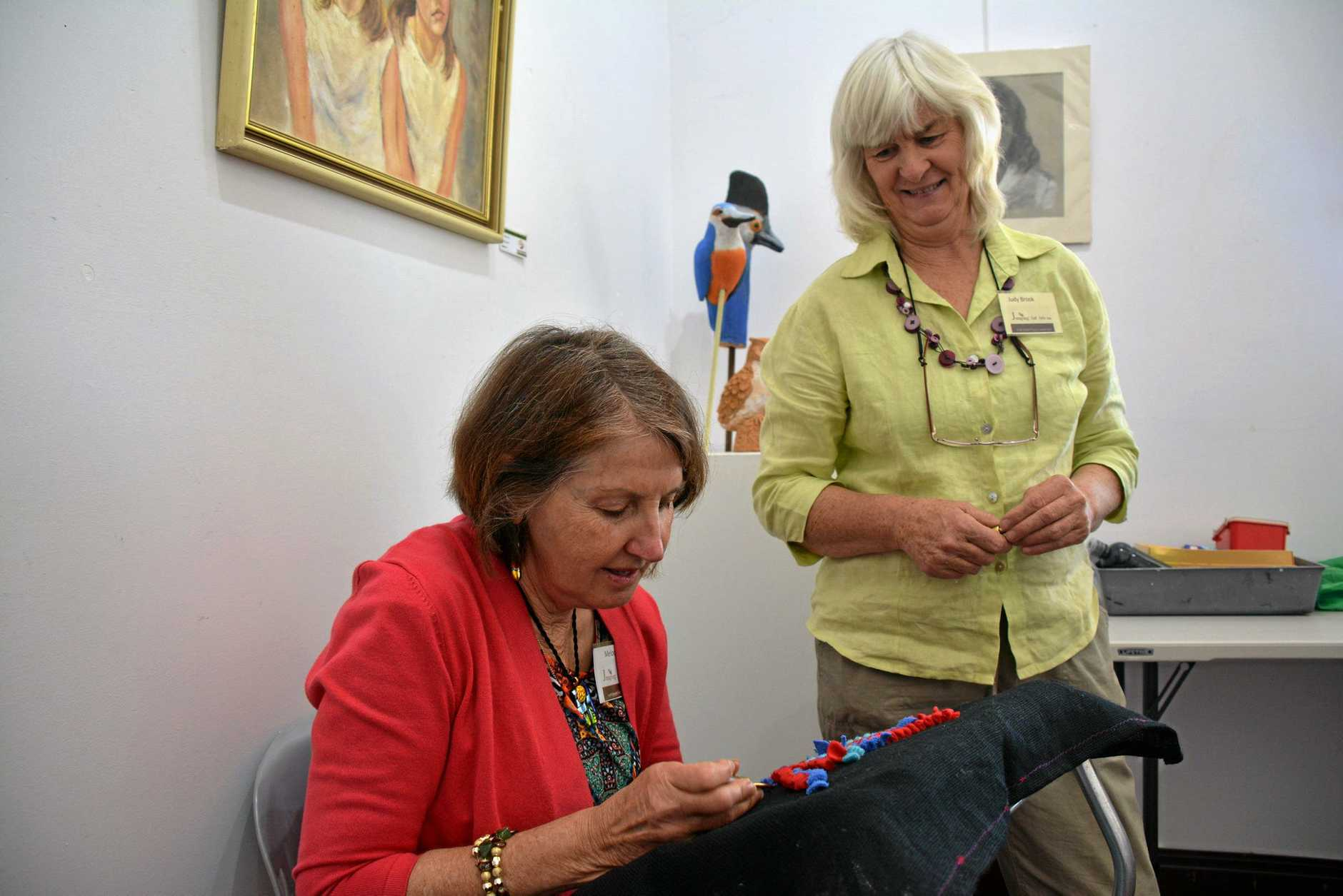 Melody Cook and Judy Brook have a go at rug hooking during the 'The Spring Collection' Jumping Ant Arts Inc.'s exhibition launch on September 4.