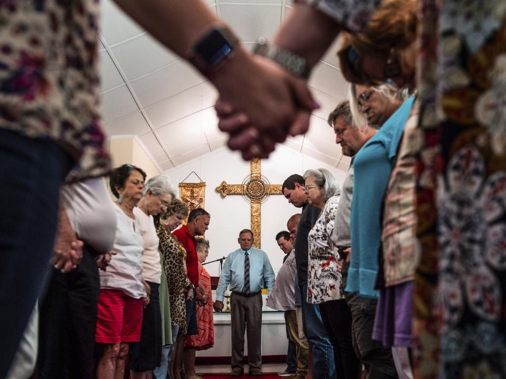 Members of the congregation at Elkmont United Methodist Church hold hands and pray. Picture: Dan Busey/The Decatur Daily via AP